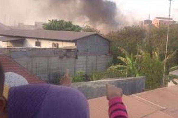 Warga menunjukkan kepulan asap dari kebakran gudang Petrokimia Gresik, Rabu (18/11/2015).