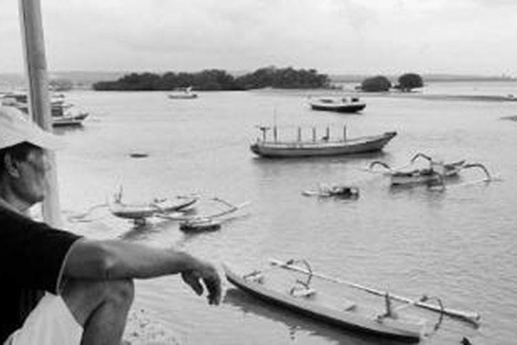 Seorang warga tengah memandang Pulau Pudut, Tanjung Benoa, Kabupaten Badung, Bali, Selasa (16/7/2013). Pulau tersebut terancam hilang akibat pengerukan dan abrasi jika tidak direklamasi kembali. Selain dimanfaatkan sebagai obyek wisata oleh masyarakat adat, pulau tersebut juga digunakan sebagai kawasan konservasi penyu.