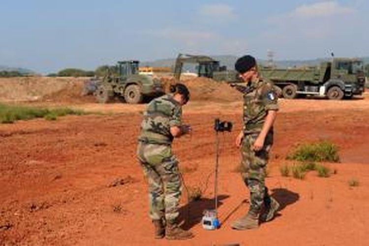 Dua prajurit Perancis tengah memeriksa kepadatan tanah yang akan digunakan sebagai lahan parkir pesawat terbang militer di areal bandar udara Bangui, Republik Afrika Tengah. Perancis berencana mengirim 1.000 prajurit dan peralatan perangnya untuk membantu negeri itu memulihkan keamanan.