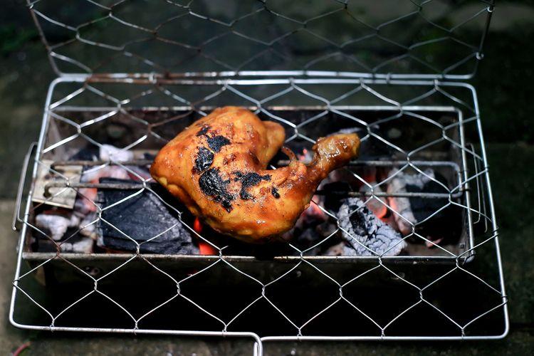 Ilustrasi proses membakar ayam di atas bar api.