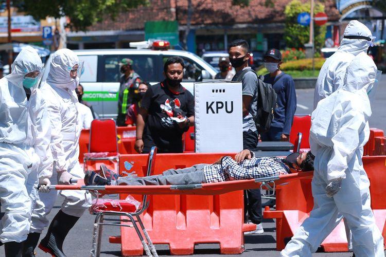 Petugas kesehatan mengangkat pemilih yang pingsan saat simulasi Pemilihan Kepala Daerah di Banyuwangi, Jawa Timur, Senin (14/9/2020). Simulasi tersebut digelar untuk menyiapkan segala hal yang diperlukan untuk penyelenggaraan Pilkada serentak pada 9 Desember 2020 di tengah wabah COVID-19. ANTARA FOTO/Budi Candra Setya/wsj.