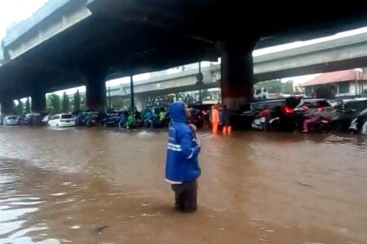 Kendaraan mengantre untuk melintas di lajur cepat Jalan DI Panjaitan, Jakarta Timur, akibat lajur lambat tergenang air hujan 30-50 centimeter, Jumat (24/1/2020).