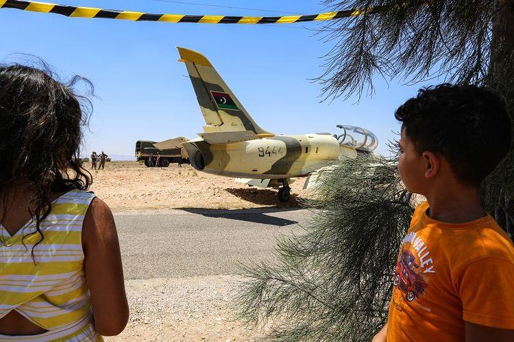 Anak-anak melihat pesawat tempur Libya milik pasukan pro-Haftar, yang mendarat darurat jalanan di Tunisia, Senin (22/7/2019).