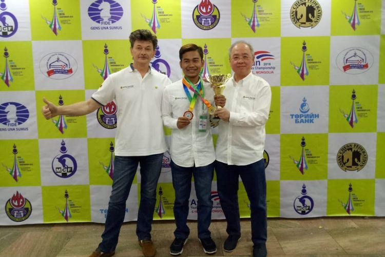 Novendra Priasmoro, diapit pelatih Andrei Kovalev dan manajer tim catur Indonesia, Kristianus Liem, merebut gelar juara Asia Junior (KU 20) pada Kejuaraan Catur Junior Asia, di Ulan Bator, Mongolia, 17-26 Agustus 2018.