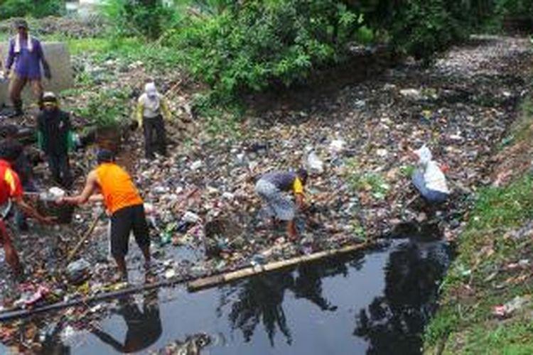 Pekerja membersihkan sampah di ujung pintu air Waduk Bujana Tirta, Pisangan Timur, Pulogadung, Jakarta Timur, Selasa (5/11/2013).