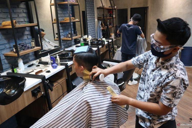 Seorang kapster sedang mencukur rambut pelanggan di Mancave Barbershop di Pasar Baru, Jakarta Pusat, Rabu (17/6/2020). Dia menggunakan alat pelindung diri berupa masker dan kacamata goggle saat bekerja untuk mencegah penularan virus COVID-19.