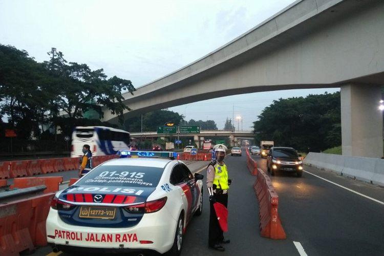 Petugas kepolisian mengatur lalu lintas di sekitar kawasan Halim yang mengarah ke lintasan Tol Dalam Kota Jakarta, Selasa (9/6/2020). Petugas menerapkan rekayasa lawan arah dalam rangka mengurangi potensi kepadatan kendaraan di sekitar Simpang Susun Cawang.