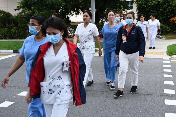 Petugas medis menyeberang menuju gedung National Centre for Infectious Diseases di RS Tan Tock Seng, Singapura, Jumat (31/1/2020).