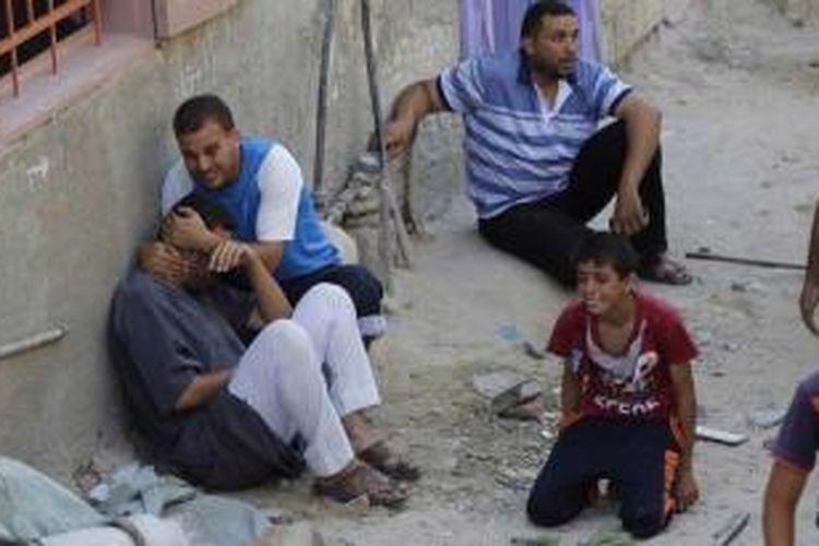 Warga Palestina tersungkur setelah sebuah serangan udara yang mematikan menghantam rumah mereka di kota Khan Yunis di jalur Gaza. serangan tersebut menewaskan puluhan warga Palestina termasuk wanita dan anak-anak.