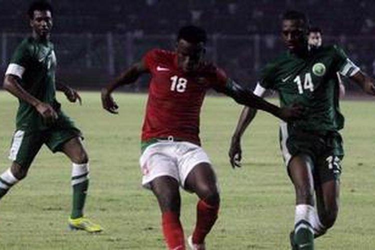 Pemain Indonesia, Greg Nwokolo (tengah), berusaha melewati hadangan pemain Arab Saudi, Saud Kariri (kanan), pada laga kedua Grup C Pra-Piala Asia Australia 2015 di Stadion Utama Gelora Bung Karno, Jakarta, Sabtu (23/3/2013). Indonesia akhirnya takluk 1-2.