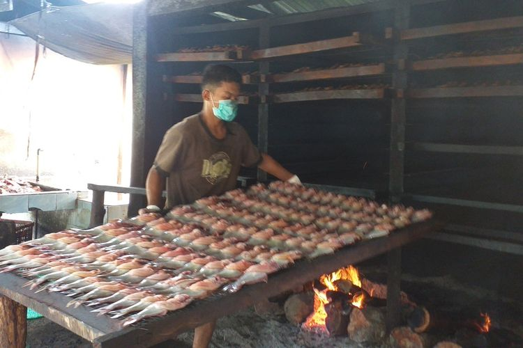 Seorang pekerja sedang melakukan proses pengasapan ikan patin di sentra pengolahan ikan patin di Kampung Patin, Desa Koto Masjid, Kecamatan XIII Koto Kampar, Kabupaten Kampar, Riau, Kamis (7/1/2021).