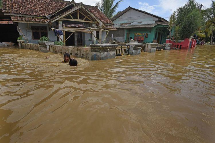 Dua anak bermain saat banjir di Kampung Nagara, Kibin Serang, Banten, Selasa (8/12/2020). Banjir akibat hujan deras tersebut meluas di tiga kabupaten di Banten dan mengakibatkan 1.423 rumah terendam serta 1.103 kepala keluarga mengungsi. ANTARA FOTO/Asep Fathulrahman/rwa.