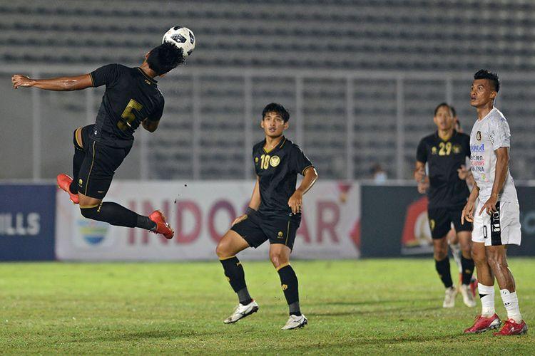 Pesepak bola Tim Nasional (Timnas) U-23 Bagas Adi Nugroho (kiri) menyundul bola saat berhadapan dengan kesebelasan Bali United dalam pertandingan uji coba di Stadion Madya, Gelora Bung Karno (GBK), Jakarta, Minggu (7/3/2021). Pertandingan dimenangkan Timnas U-23 dengan skor 3-1.