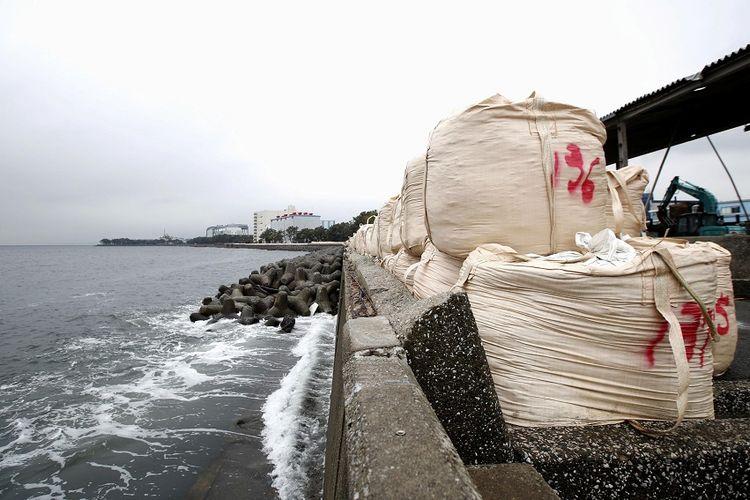 Karung pasir ditumpuk di tembok laut sebagai persiapan untuk menghadapi Topan Hagibis di pantai di Yokohama, Jepang, Jumat (11/10/2019).