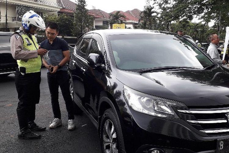 Seorang pengendara Honda CRV berpelatnomor B 1344 BJM terkena razia penesahan STNK di Jalan Puri Indah, Kembangan, Jakarta Barat pada Rabu (28/11/2018).