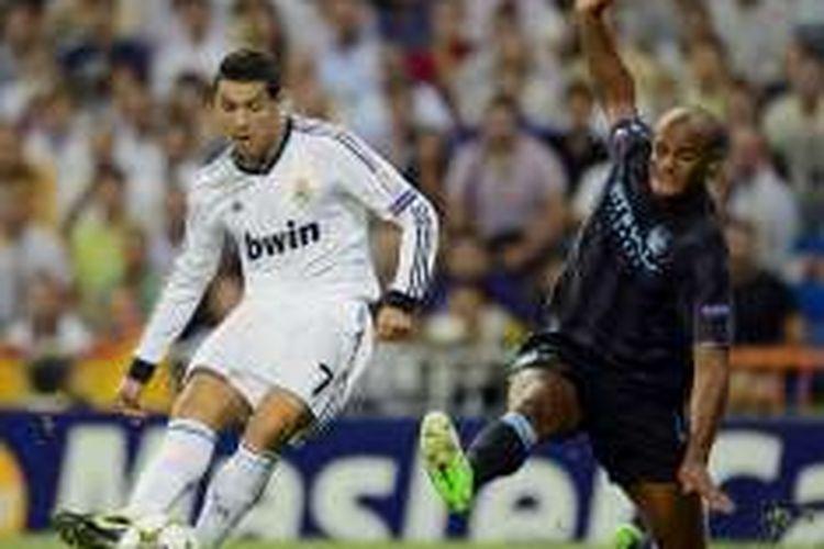 Pemain Real Madrid, Cristiano Ronaldo, berduel dengan bek Manchester City, Vincent Kompany, pada laga penyisihan grup Liga Champions musim 2012-2013.