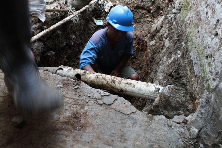 Pekerja menggali tanah yang sudah diberi titik untuk pembuatan septik tank di Gang Sekretaris I, Tanjung Duren Jakarta Barat, Rabu (9/10/2019). Ada sekitar 21 titik lubang galian yang dibuat di sepanjang gang.