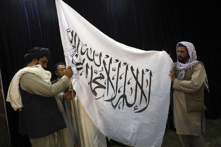 Anggota Taliban memasang bendera kelompok mereka sebelum konferensi pers juru bicara Zabihullah Mujahid, di Pusat Informasi Media Pemerintah, Kabul, Afghanistan, Selasa (17/8/2021).