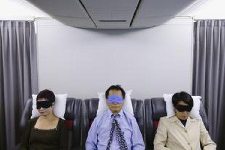 Tidur di pesawat.
