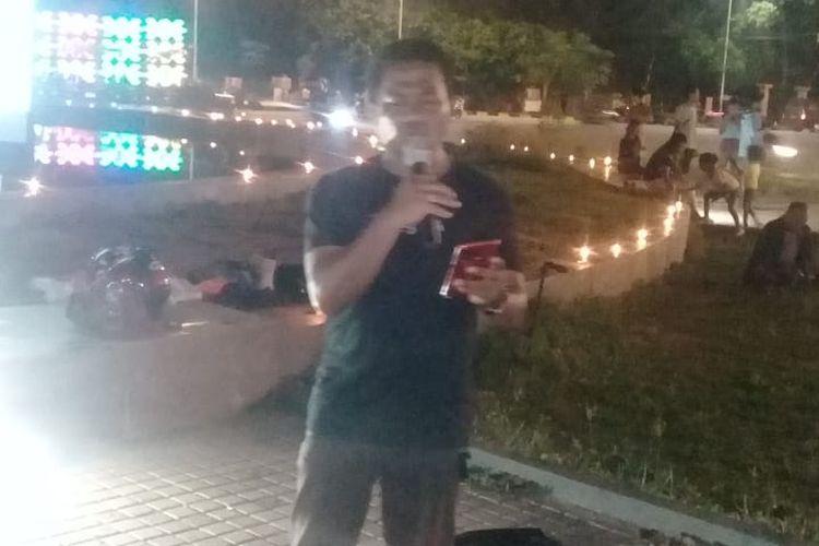 Ketua Forum Peduli Martabat Guru (FPMG) NTT Beny Mauko, saat berorasi dengan latar belakang 1.001 lilin yang dibakar mengelilingi Bundara Patung Tirosa, Rabu (11/3/2020) malam.