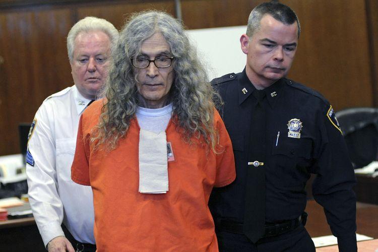 Dalam foto bertanggal 7 Januari 2013, nampak pembunuh berantai Rodney Alcala dibawa keluar dari Pengadilan New York, Amerika Serikat (AS). Alcala dijatuhi hukuman mati hingga 25 tahun penjara setelah terbukti membunuh empat perempuan dan seorang remaja 12 tahun di New York dan California.