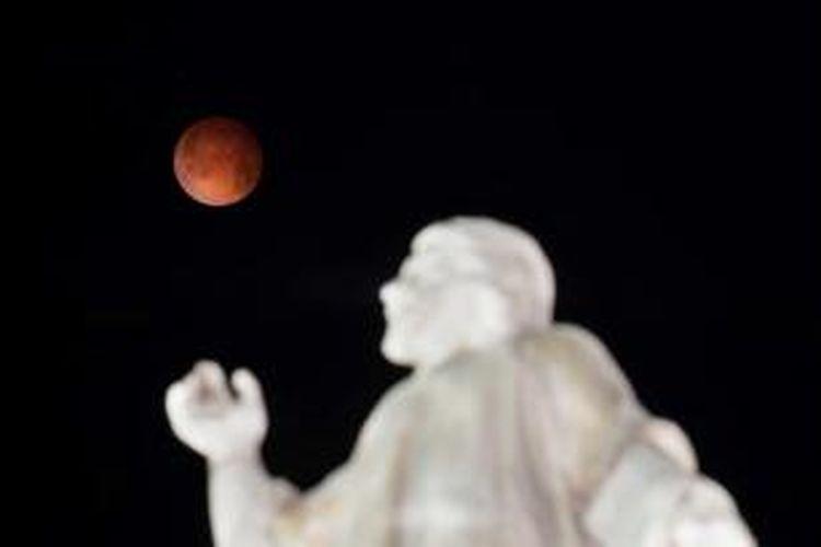 Gerhana bulan terlihat dengan latar depan Monumen El Salvador del Mundo di San Salvador, El Salvador, 15 April 2014. Gerhana bulan kali ini terbilang langka karena bulan berubah warna dari oranye ke merah darah.