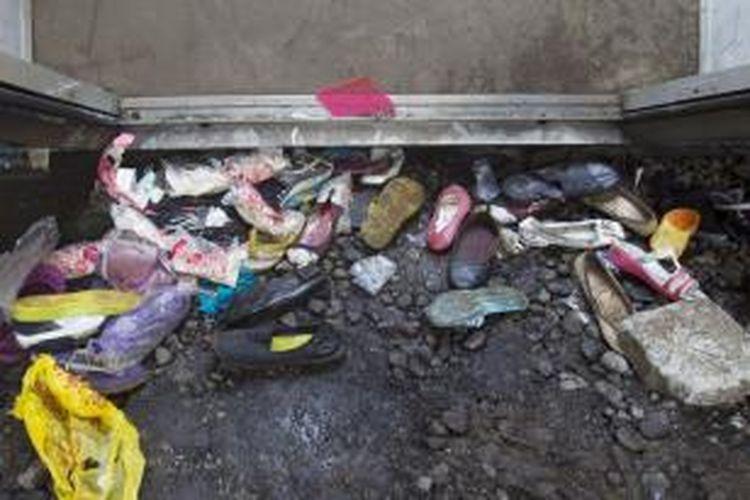 Alas kaki korban yang tertinggal di lokasi tabrakan kereta rel listrik (KRL) jurusan Serpong-Tanah Abang dengan truk tangki pengangkut bahan bakar di pelintasan Pondok Betung, Bintaro, Jakarta Selatan, Senin (9/12/2013). Kecelakaan mengakibatkan sejumlah rangkaian gerbong dan truk tangki terbakar, menyebabkan puluhan orang luka-luka dan 10 orang tewas.