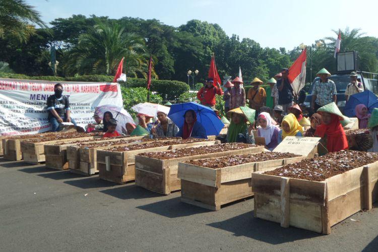 Aksi kubur diri petani Telukjambe di depan Halaman Monumen Nasional, Jakarta Pusat, Senin (1/5/2017)