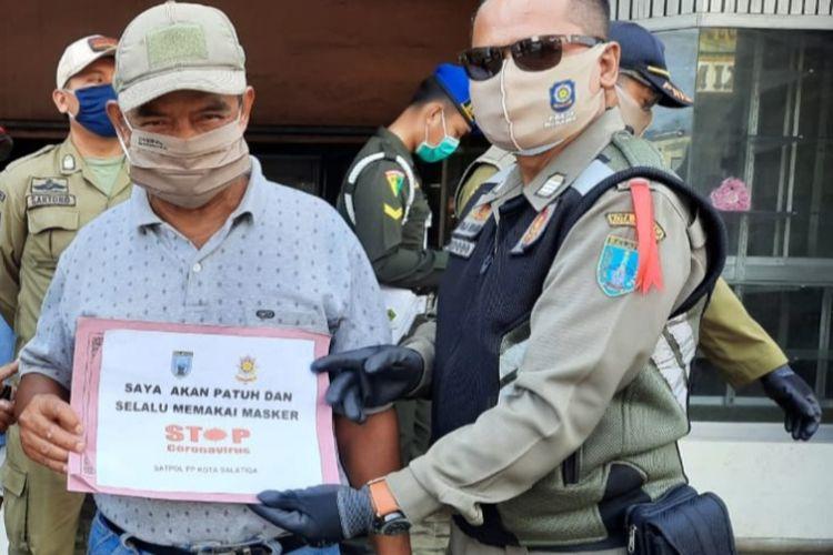 Warga yang tidak memakai masker diharuskan foto menggunakan papan pernyataan.