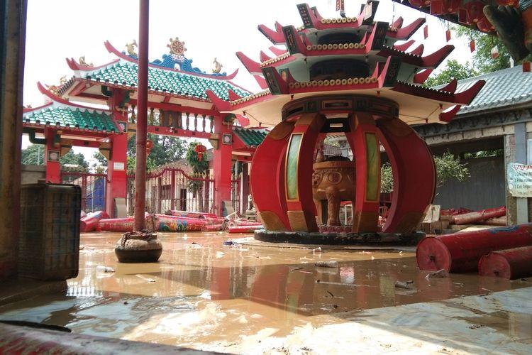 Locu Kelenteng Sian Djin Kupoh Astri Supriatin tengah membersihkan bagian kelenteng yang terendam banjir, Selasa (23/2/2021).