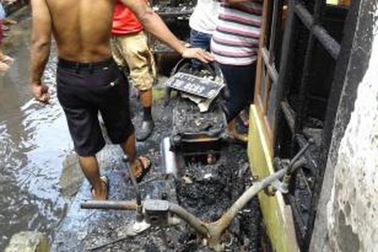 Sebuah motor tidak berhasil diselamatkan saat kebakaran terjadi di RT 14 RW 05 Tanjung Duren Selatan, Grogol Petamburan, Jakarta Barat, Kamis (13/11/2014). Motor kesulitan dibawa keluar karena kondisi jalan yang penuh sesak warga yang panik dan api yang menyambar dari arah atas.