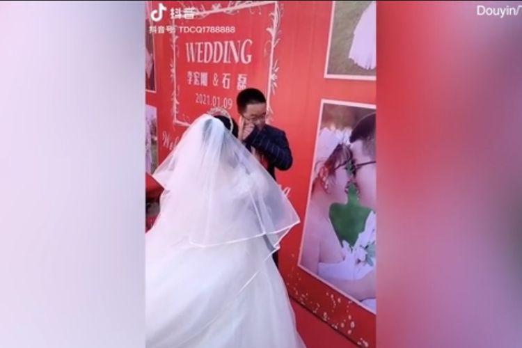 Pengantin pria yang diidentifikasi bernama Tuan Li menangis dengan istrinya, Shi, harus menenangkannya. Li menangis dan meminta maaf karena tidak ada keluarga dan teman-teman mereka yang datang ke resepsi, buntut pemberlakuan Covid-19 yang dilakukan pemerintah China.(Screengrab Douyin via Daily Mail)