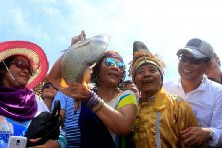 Menteri Kelautan dan Perikanan Susi Pujiastuti memperlihatkan ikan yang baru saja ditangkapnya saat menghadiri Festival Mane'e di Pulau Intata, Kecamatan Nanusa, Kabupaten Talaud, Sulawesi Utara, Kamis (7/5/2015).