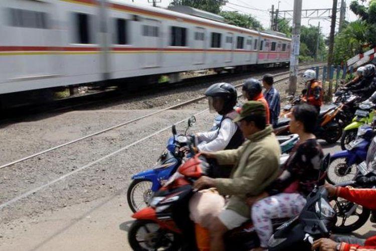Pengendara motor berhenti di perlintasan kereta api di sekitar Pasar Bintaro, Pesanggrahan, Jakarta Selatan, Kamis (4/4/2013). Pertemuan lalu lintas dari empat arah di pintu perlintasan itu menjadi penyebab kemacetan. Kondisi ini tentunya menyebabkan kawasan itu rawan kecelakaan yang melibatkan kereta api.