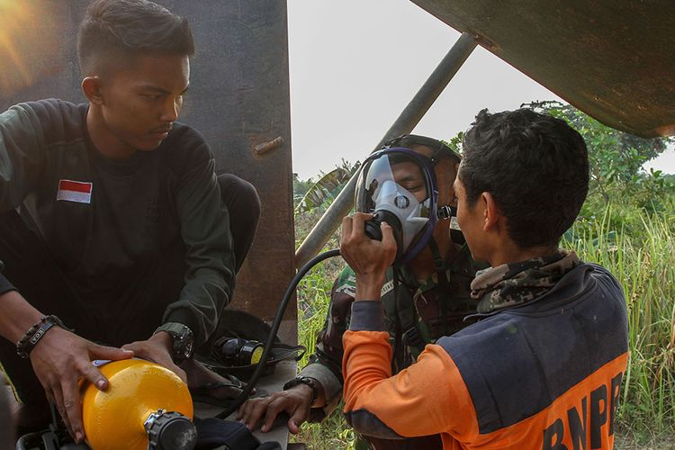 Petugas Badan Penanggulangan Bencana Daerah (BPBD) Pekanbaru memberikan bantuan oksigen kepada prajurit TNI dari Kodim 0301 Pekanbaru saat berupaya memadamkan kebakaran lahan gambut di Pekanbaru, Riau, Sabtu (7/9/2019). Pekatnya asap di lokasi lahan gambut yang terbakar membuat petugas gabungan merasa sesak napas karena terlalu banyak menghirup asap sehingga sempat menyulitkan petugas untuk memadamkan kebakaran tersebut.