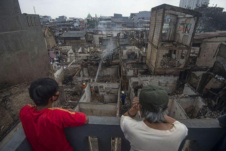 Dua warga mengamati puing-puing rumah yang hangus terbakar di perkampungan padat penduduk di Duri Selatan, Tambora, Jakarta Barat, Jakarta, Rabu (12/8/2020). Kebakaran tersebut mengakibatkan sebanyak 974 warga di empat rukun tetangga (RT) kehilangan tempat tinggal dan satu pasar tradisional terbakar.