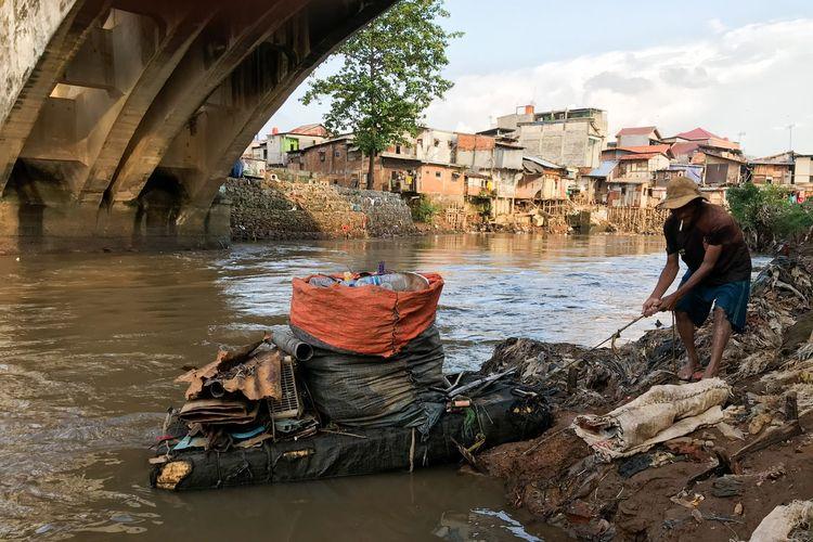 Suparno (69) atau dikenal dengan sebutan Pak Kentir tengah melabuhkan pelampung yang berbentuk seperti perahu di pinggir Sungai Ciliwung tepatnya di bawah jembatan bersejarah di kawasan Manggarai, Tebet, Jakarta Selatan pada Jumat (12/3/2021) sore. Pak Kentir sehari-hari mencari sampah dan barang rongsok untuk dijual demi memenuhi kebutuhan sehari-hari.