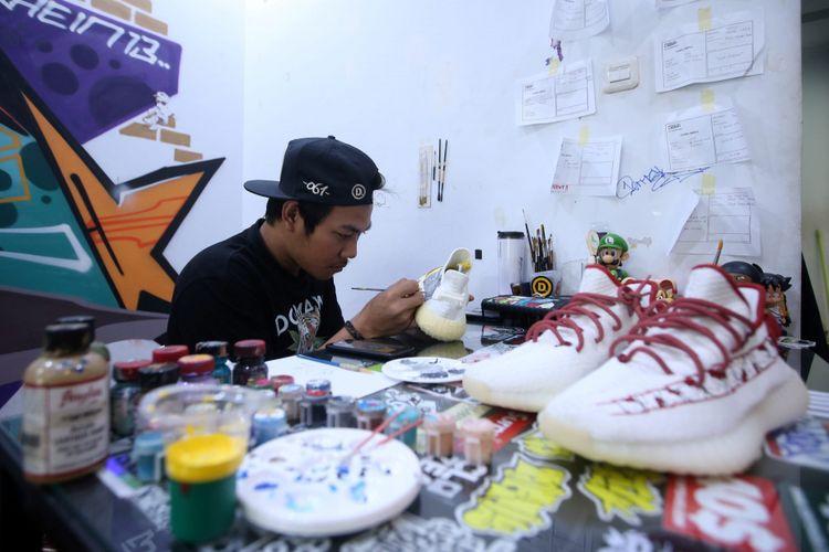 Seniman Never Too Lavish menyelesaikan proses melukis sepatu di studio Never Too Lavish, Jakarta, Selasa (10/4/2018). Belakangan nama Never Too Lavish mencuri perhatian setelah karyanya di jaket denim digunakan Presiden Joko Widodo saat turing dengan sepeda motor di Sukabumi.