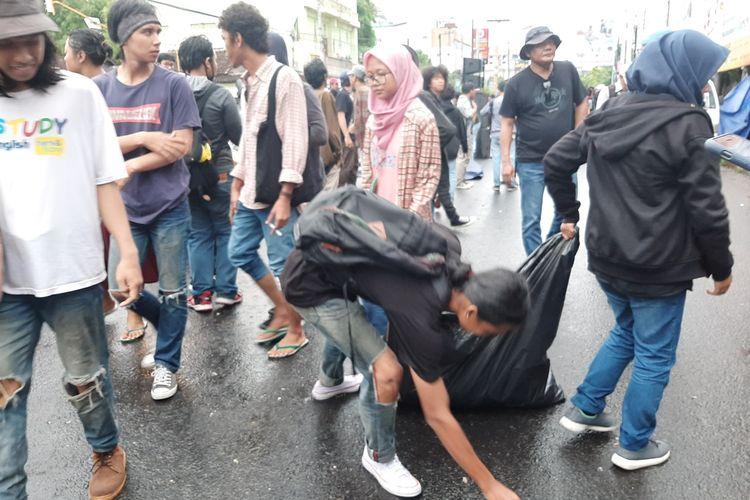 Beberapa peserta aksi, saat mengambil sampah di Simpang Tiga Gejayan.