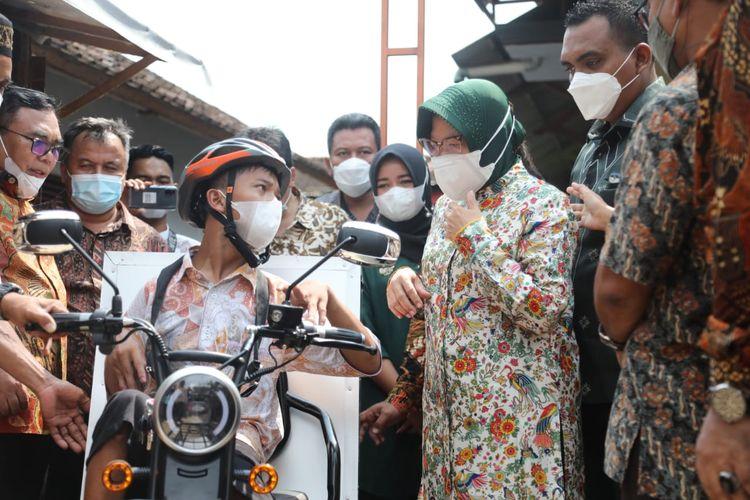 Menteri Sosial Tri Rismaharini Menyerahkan sepeda motor roda tiga kepada penyandang disabilitas fisik Gading Ogi Saputra (17) di Pekalongan, Minggu (16/5/2021).