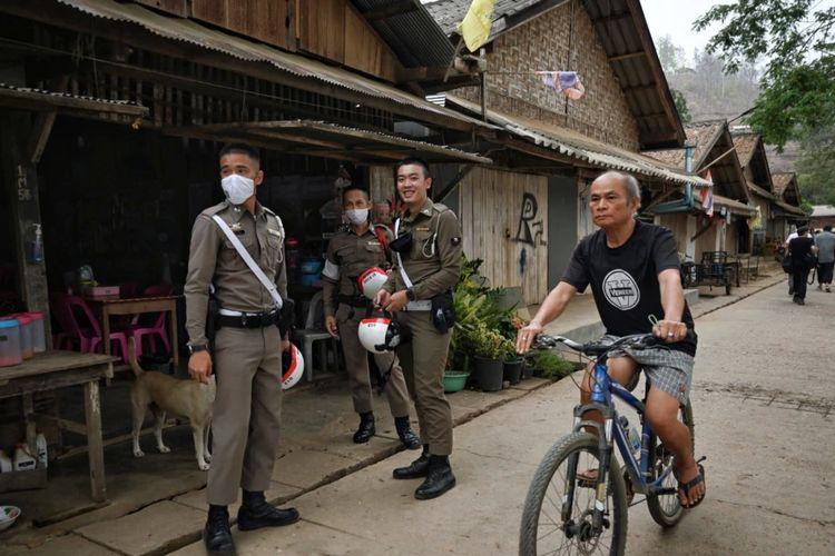 Seorang migran Karen yang tinggal di Thailand bersepeda melewati polisi Thailand di kota Mae Sam Laep di sisi sungai Salween di Thailand di provinsi Mae Hong Son pada 2 April 2021, di seberang tempat pengungsi Myanmar sebelumnya berusaha melintasi perbatasan Thailand.