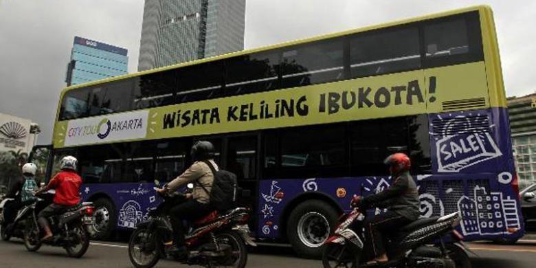 Bus tingkat wisata melintas di sekitar Bundaran HI, Jakarta Pusat, untuk diperkenalkan kepada masyarakat, Kamis (16/1/2014). Pemprov DKI Jakarta mendatangkan lima bus tingkat dari China untuk meningkatkan pariwisata, yang akan mulai dioperasikan awal Februari.