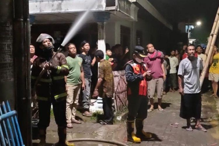 Petugas berusaha memadamkan sisa percikan api dalam peristiwa kebakaran yang melanda rumah warga di Kota Tegal, Jawa Tengah akibat memasak ketupat dengan kayu bakar yang ditinggal tidur, Rabu (12/5/2021) malam.