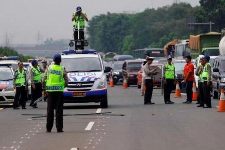 Polisi melakukan olah TKP kecelakaan yang melibatkan dua mobil di KM 8,2 Jalan Tol Jagorawi, Jakarta Timur, Minggu (8/9/2013) dini hari.