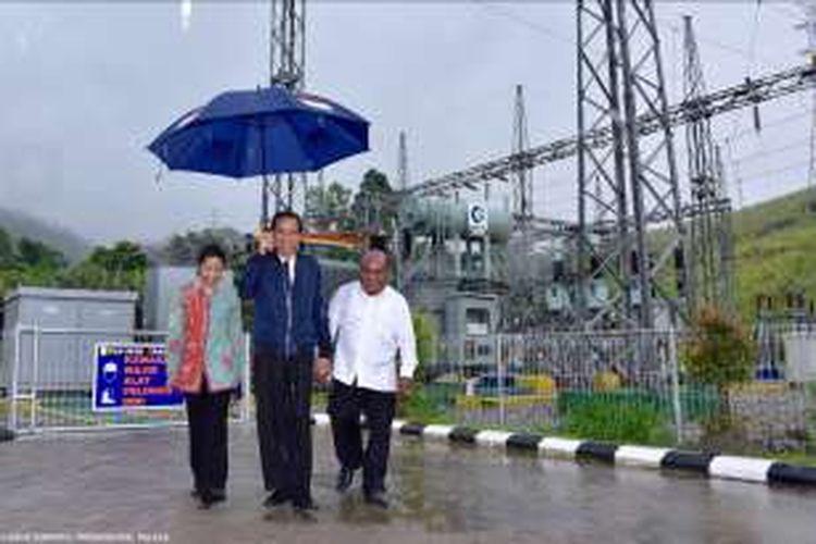 Presiden Jokowi memegang payung sendiri didampingi Menteri BUMN Rini Soemarno dan Gubernur Papua Lucas Enembe ketika meninjau Gardu Induk baru yang mengaliri listrik di sekitar Sentani dan Jayapura, Senin (17/10/2016). Presidential Palace/Agus Suparto