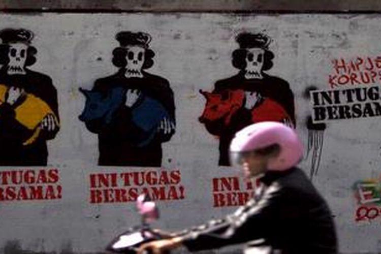 Pengendara sepeda motor melintas di depan mural berisi imbauan untuk menghapus korupsi bersama di kawasan Senayan, Jakarta Selatan, Kamis (16/5/2013). Kritikan terhadap pelaku koruptor terus disuarakan oleh aktivis untuk mendorong tindakan lebih tegas dalam pemberantasan korupsi dan penegakan hukum lainnya.