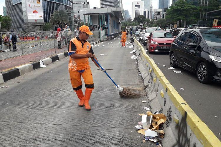 Petugas PPSU membersihkan sampah yang ditinggalkan massa peserta aksi Hari Buruh Internasional di Jalan Jenderal Sudirman kawasan Tosari, Rabu (1/5/2019)?
