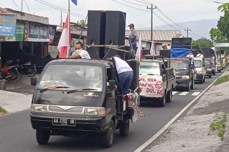 Konvoi puluhan mobil bak terbuka dan truk yang memuat beragam peralatan musik, tenda hingga sound system terjadi di sepanjang jalan protokol di Kabupaten Magelang, Jawa Tengah, Senin (30/8/2021).