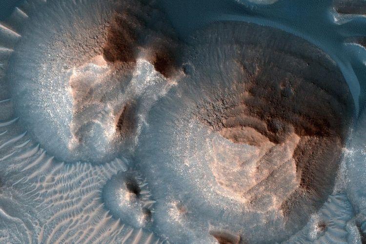 Beberapa kawah di Arabia Terra, planet Mars yang dipenuhi dengan batuan berlapis, sering tersingkap dalam gundukan bulat. Gambar itu diambil kamera, Eksperimen Pencitraan Resolusi Tinggi, di Mars Reconnaissance Orbiter NASA. Ilmuwan NASA mengkonfirmasi adanya ribuan letusan gunung berapi purba di Mars.