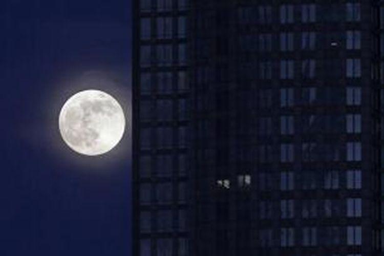 Bulan purnama naik di samping sebuah gedung perkantoran di pusat kota Charlotte, NC, 22 Juni 2013. Bulan yang akan mencapai tahap penuh pada Minggu, 13.5 persen lebih dekat ke bumi dan dikenal sebagai fenomena supermoon.
